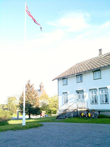 Dønnes gård med Dønnes kirke i bakgrunnen.