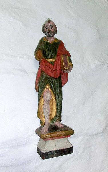 Alle de gamle katolske figurene har fått armene kappet av. Det er det en historie bak, og den får du høre hvis du besøker Dønnes Kirke. Denne figuren er forøvrig St. Laurentsius.