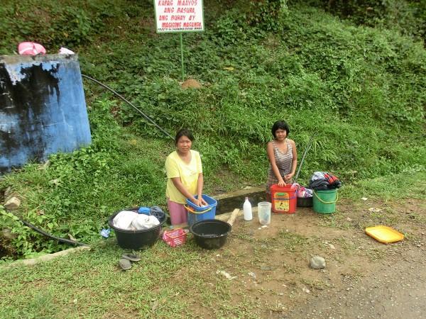 Langs veien sto to kvinner og vasket klær ved en vannpumpe