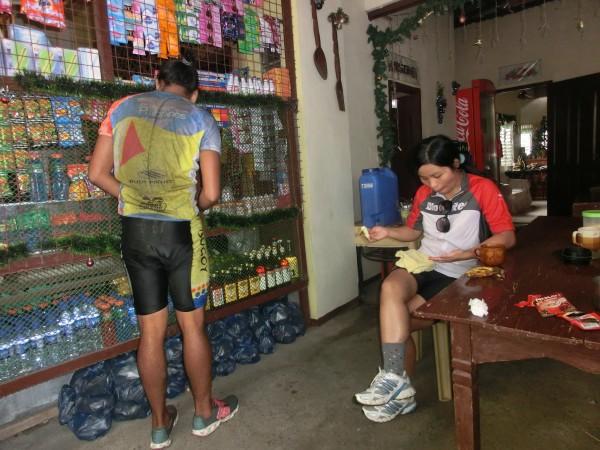 """(10:12) Her i denne lille kafeen kjøpte vi varm """"kaffe"""" som ble servert i kopper som kun var skylt i kalt vann etter forrige bruker. Legg merke til ryggen på følgesyklisten fra Bugoy Bikers. Det er mye """"dritt"""" som spruter opp fra hjulene."""