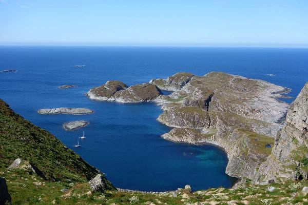 På yttersia av Sanna er det en fin liten bukt der to seilbåter har ankret opp i det gode været.