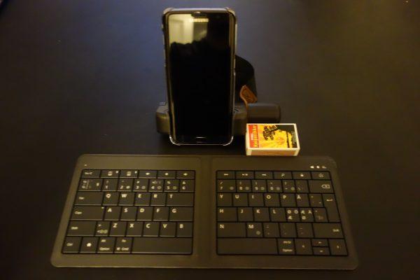 Min blogg-plattform på tur. En Samsung Galaxy S7 og et sammenleggbart Microsoft tastatur (Microsoft Foldable Keyboard). Fyrstikkesken er lagt der for å ha noe å vise størrelsen i forhold til - det er en standard fyrstikkeske.